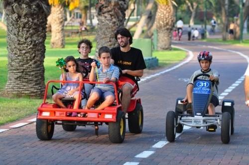 משפחה נוסעת על מכונית פדלים חשמלית אדומה ליד ילד שנוסע על מכונית פדלים חשמלית כחולה