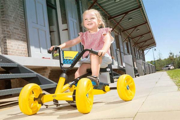 ילדה רוכבת על מכונית פדלים צהובה