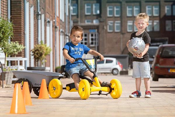 שני ילדים משחקים עם מכונית פדלים כתומה