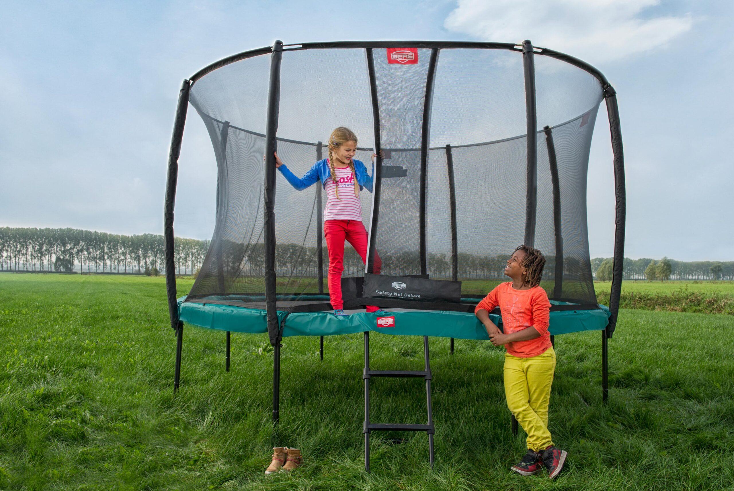 ילד וילדה משחקים בטרמפולינת ברג צ'מפיון עם רשת ביטחון בצבע ירוק