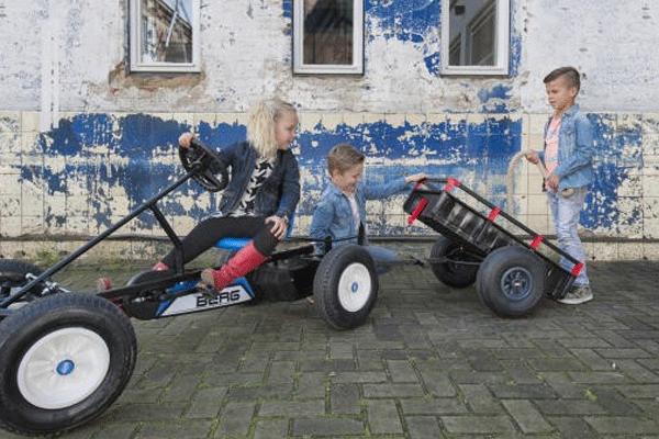 מכונית פדלים חשמלית עם נגרר ושלושה ילדים משחקים