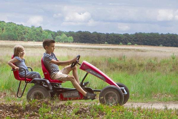 שני ילדים רוכבים על מכונית פדלים אדומה בשטח
