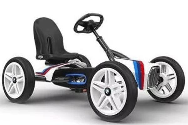 מכונית פדלים לבנה עם כסא שחור ופסים בצבעי פסטל