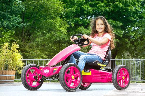 ילדה רוכבת על מכונית פדלים חשמלית בצבע ורוד
