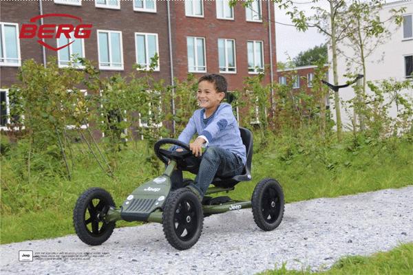 ילד נוסע על מכונית פדלים מדגם ג'יפ על דרך חצץ
