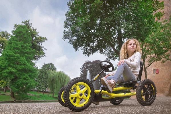 ילדה נוסעת על מכונית פדלים עם עצים ברקע