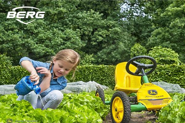 ילדה משחקת בגינה עם מכונית פדלים ג'ון דיר