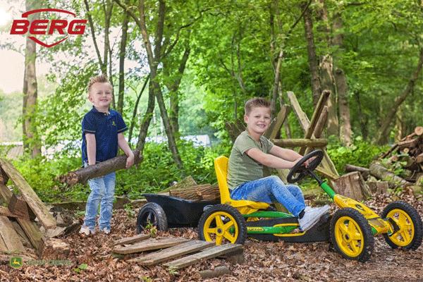 ילדים משחקים ביער עם מכונית פדלים מדגם באדי ג'ון דיר