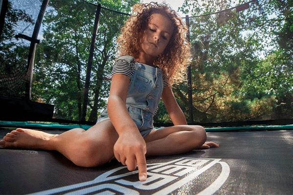 ילדה יושבת על משטח טרמפולינה