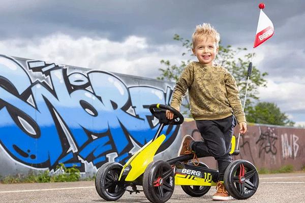 ילד עם מכונית פדלים צהובה דגם ברג באזי אירו