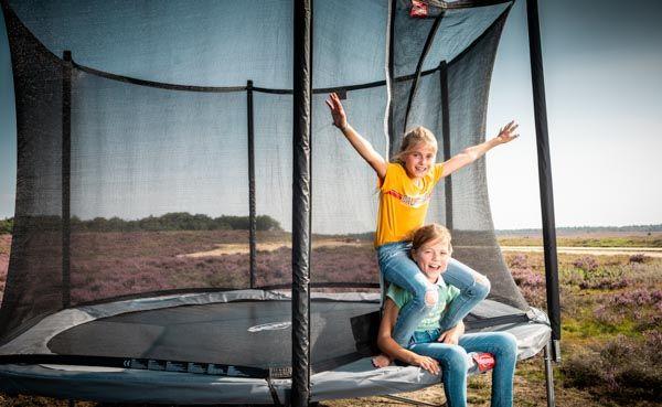 שני ילדים יושבים על קצה של טרמפולינה